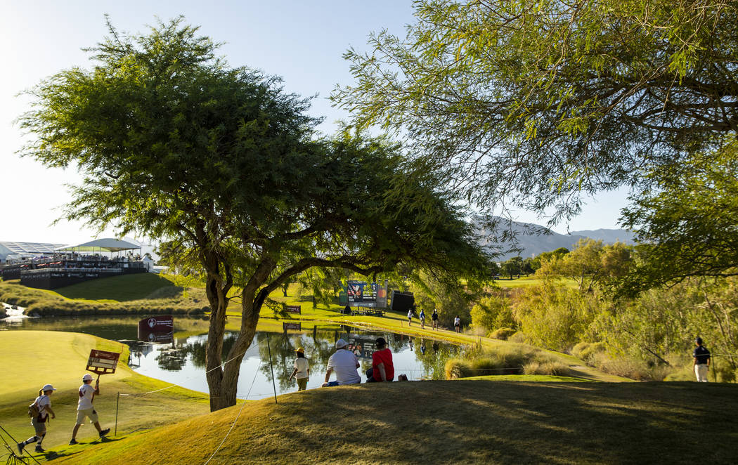 Gallery members take in the day at a water feature alongside the hole 18 fairway during the thi ...