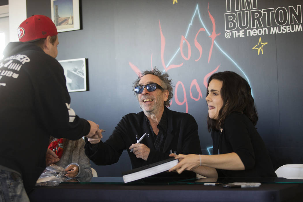 Director and artist Tim Burton, middle, greets fans during a book signing promoting his exhibit ...