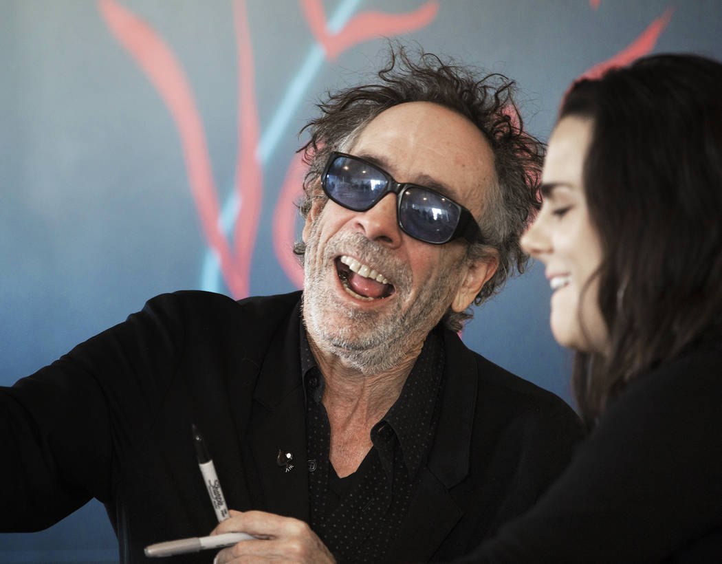 Director and artist Tim Burton, left, greets fans during a book signing promoting his exhibitio ...