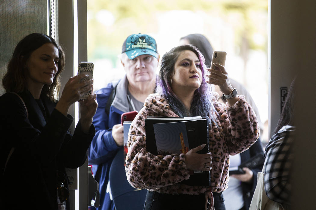 Mayra Nicola, middle, from Los Angeles, Calif., waits in line to meet director and artist Tim B ...