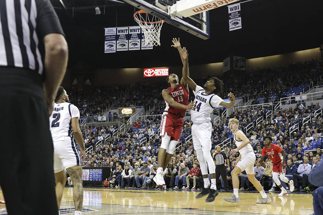 UNLV Rebels' Bryce Hamilton (13) goes to the basket against UNR's Lindsey Drew (14) during the ...