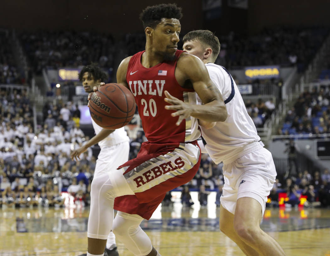 UNLV Rebels' Nick Blair (20) moves the ball around a UNR defender during the first half of a ba ...