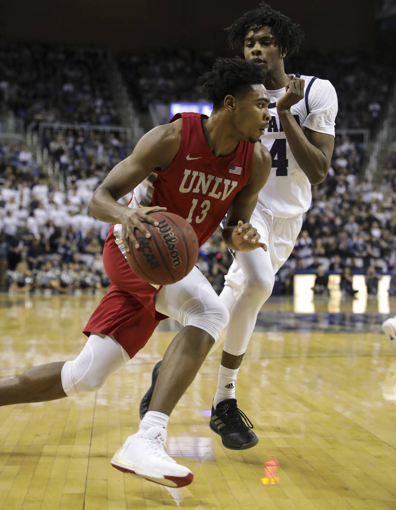 UNLV Rebels' Bryce Hamilton (13) drives to the basket against UNR's Lindsey Drew (14) during th ...