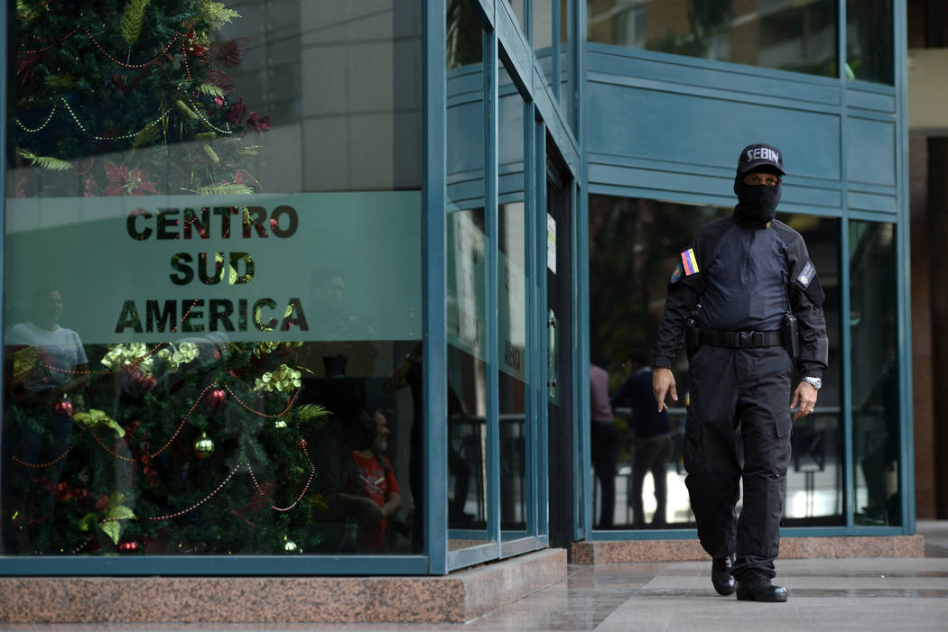 A Venezuelan security officer guards the entrance, after other officers entered the building wh ...