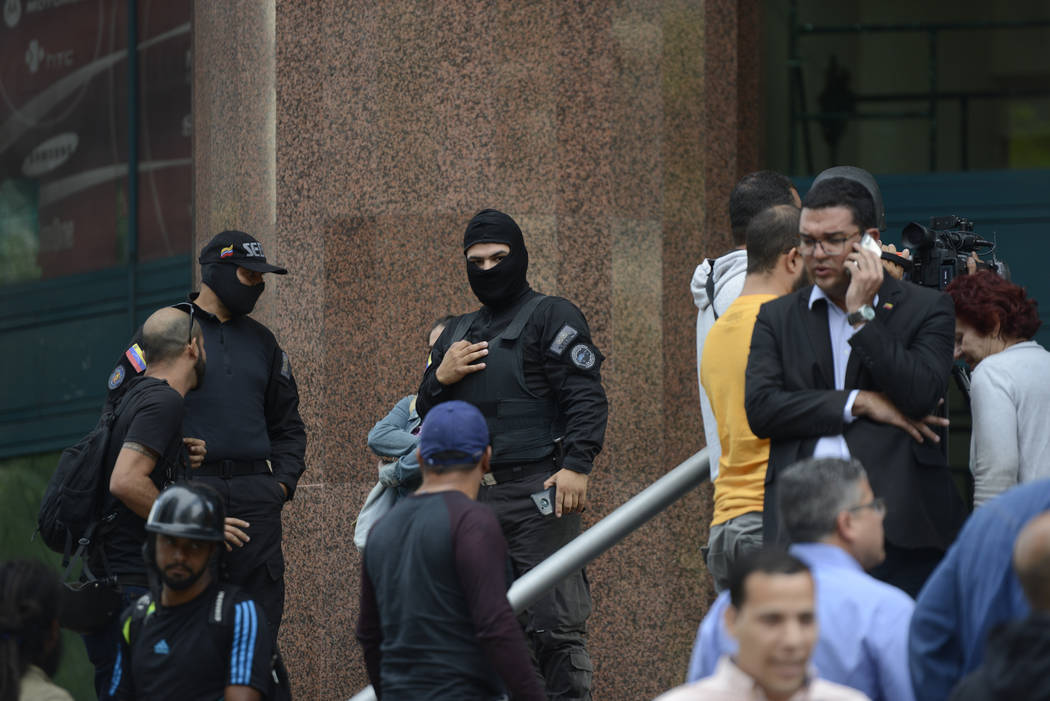Venezuelan security officers block the entrance into the building where the offices of Venezuel ...