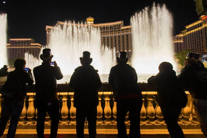 People watch the Bellagio fountain show on the Strip on New Year's Eve, Tuesday, Dec. 31, 2019, ...
