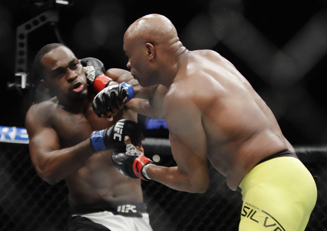 Anderson Silva, of Brazil, right, punches Derek Brunson during a middleweight mixed martial art ...