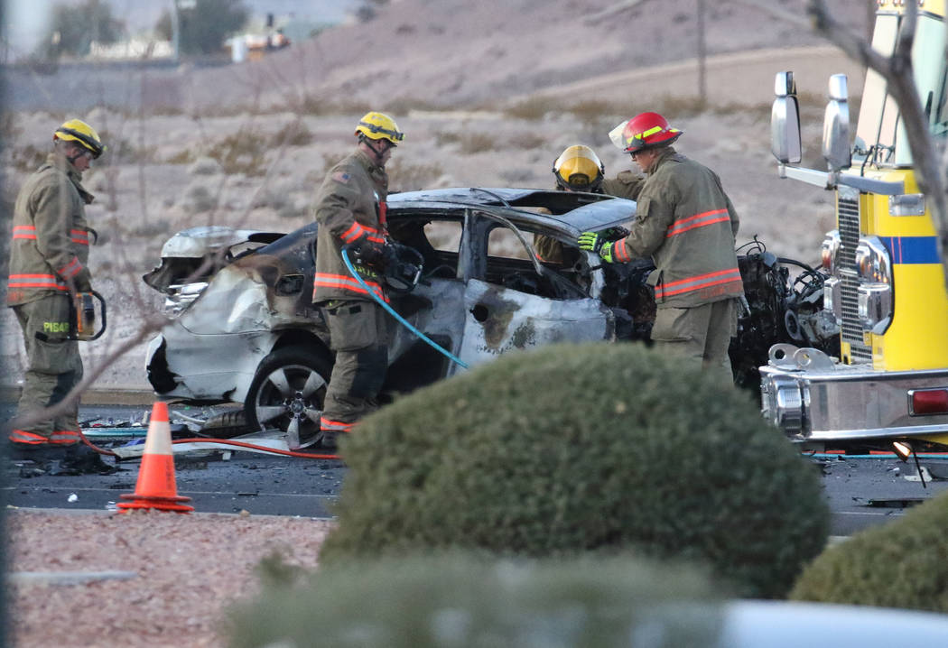 Clark County firefighters work at a three-vehicle crash site where one motorist was killed and ...