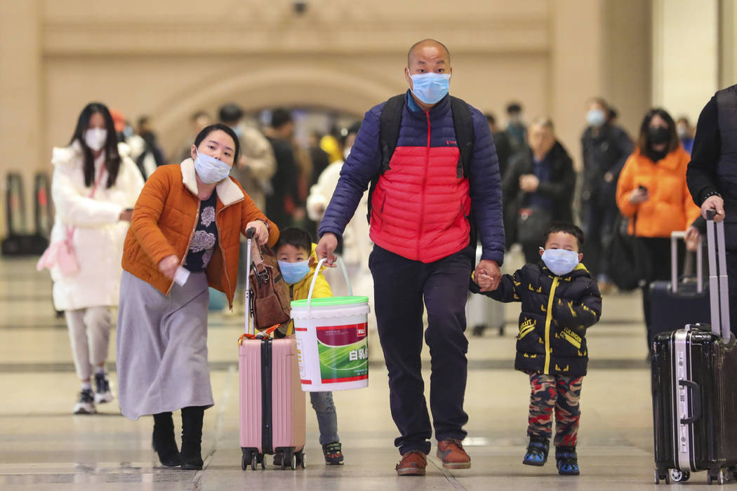 In this photo taken Tuesday, Jan. 21, 2020, travelers wearing face masks walk with their luggag ...