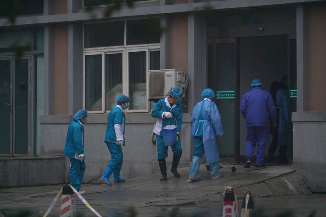 Hospital staff wash the emergency entrance of Wuhan Medical Treatment Center, where some infect ...
