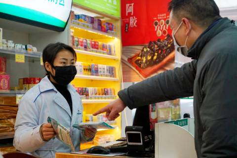 Staff sell masks at a Yifeng Pharmacy in Wuhan, Chin, Wednesday, Jan. 22, 2020. Pharmacies in W ...