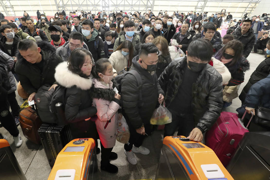 Travelers wear face masks as they line up at turnstiles at a train station in Nantong, eastern ...