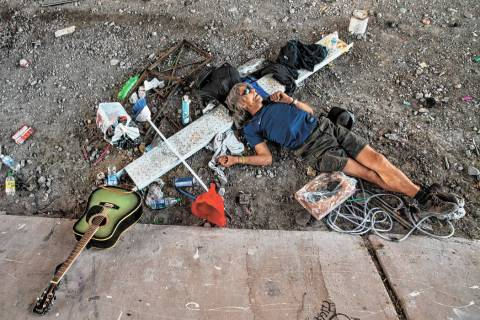 A homeless individual takes a nap beside some possessions below the Flamingo Road overpass on T ...