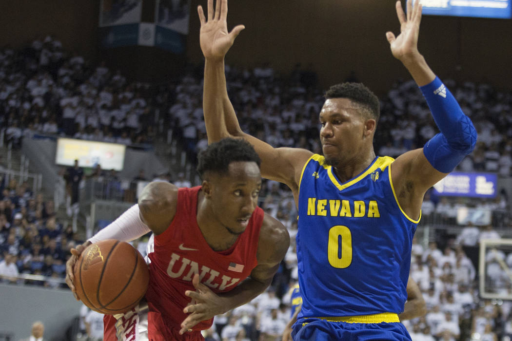 UNLV guard Kris Clyburn (1) drives on Nevada forward Tre'Shawn Thurman (0) during the first hal ...