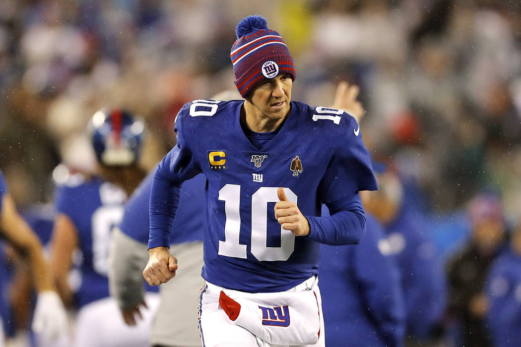 New York Giants quarterback Eli Manning (10) runs on the sideline in the second half of an NFL ...