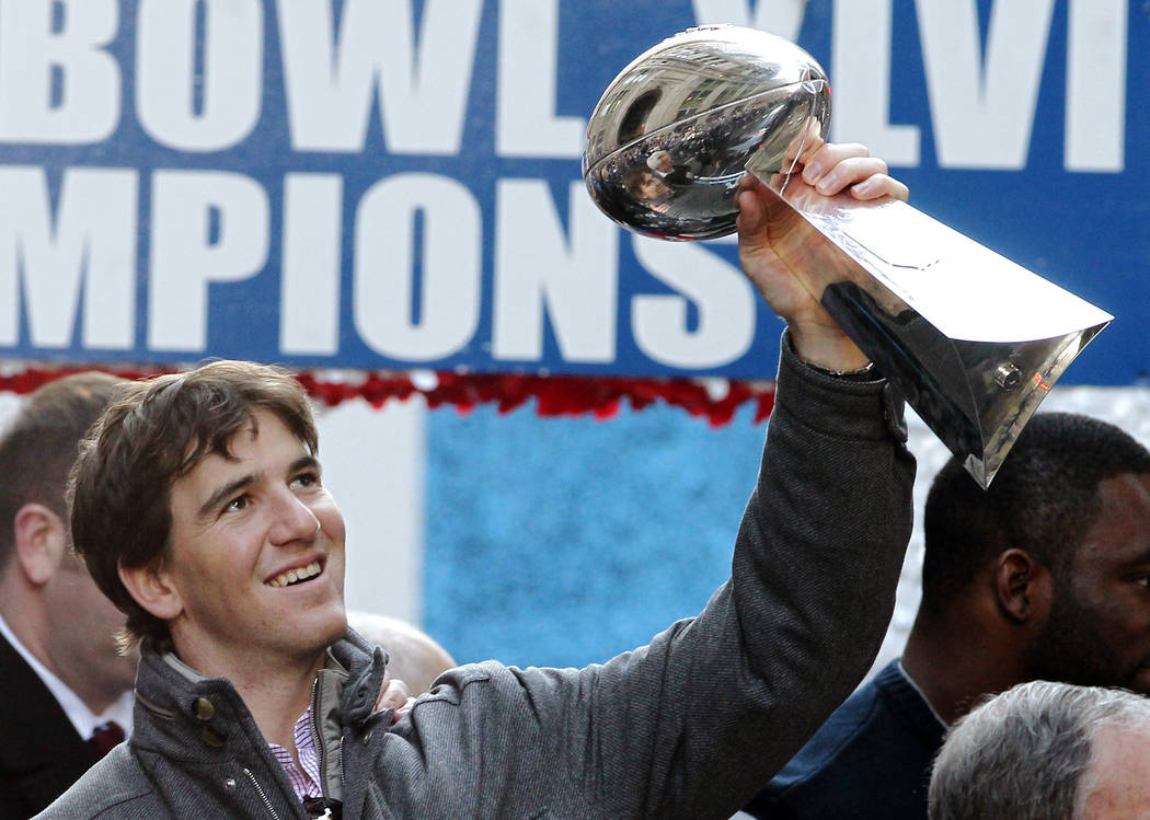 File-This Feb. 7, 2012, file photo shows New York Giants quarterback Eli Manning holding up the ...