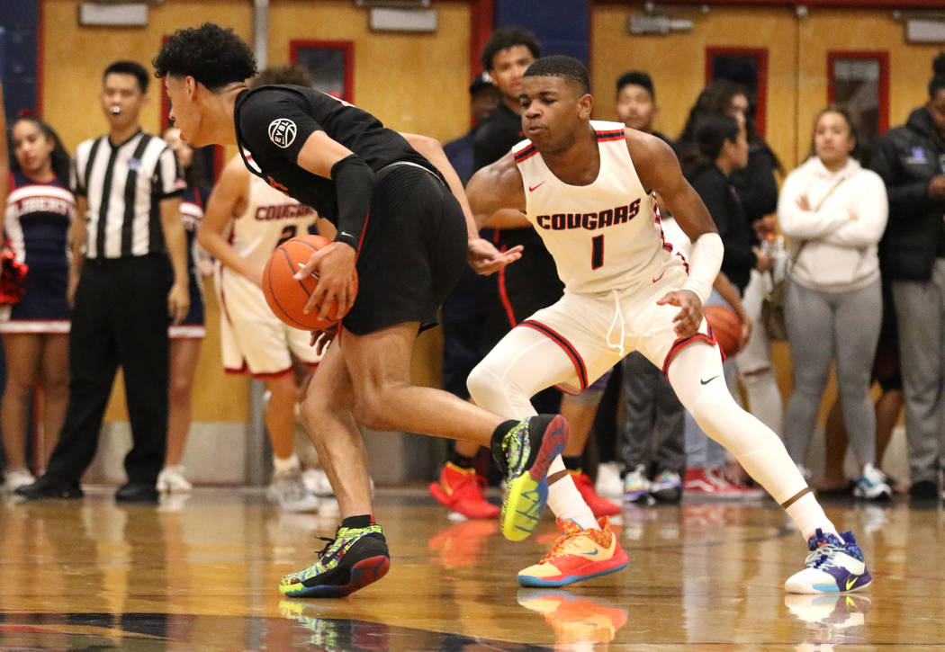 Coronado High's Jaden Hardy (1) defends Liberty High's guard Julian Strawther (0) during the th ...
