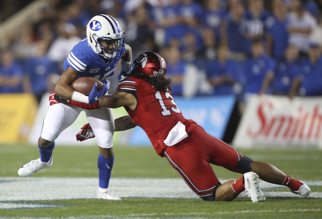 BYU wide receiver Aleva Hifo (15) is tackled by Utah linebacker Francis Bernard (13) during the ...
