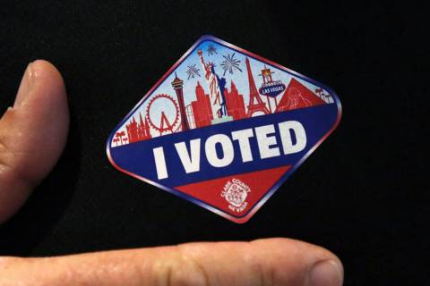"A man shows off his ""I Voted"" sticker after casting his ballots at a polling station at Galleri ..."