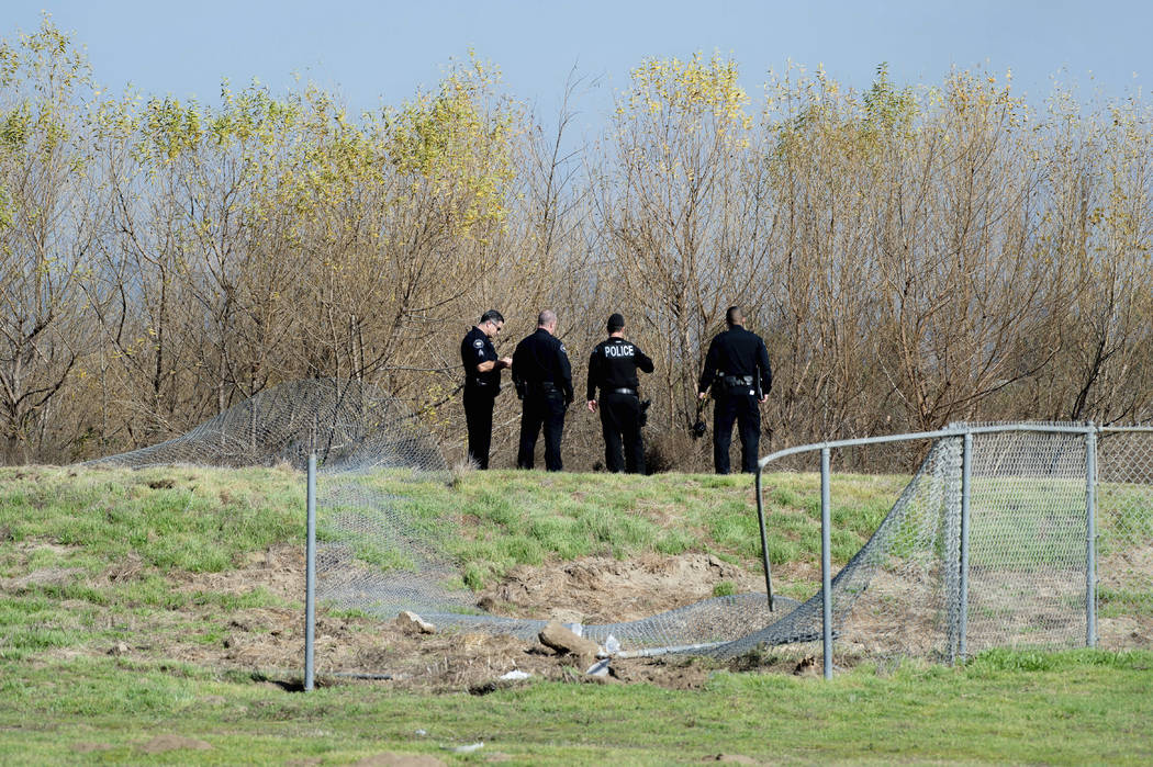 Corona Police officers survey the site where an airplane crashed and burned in a ditch next to ...