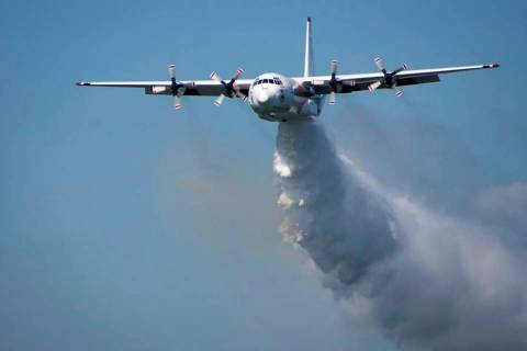 "A C-130 Hercules plane called ""Thor"" drops water during a flight in Australia. (RFS via AP)"