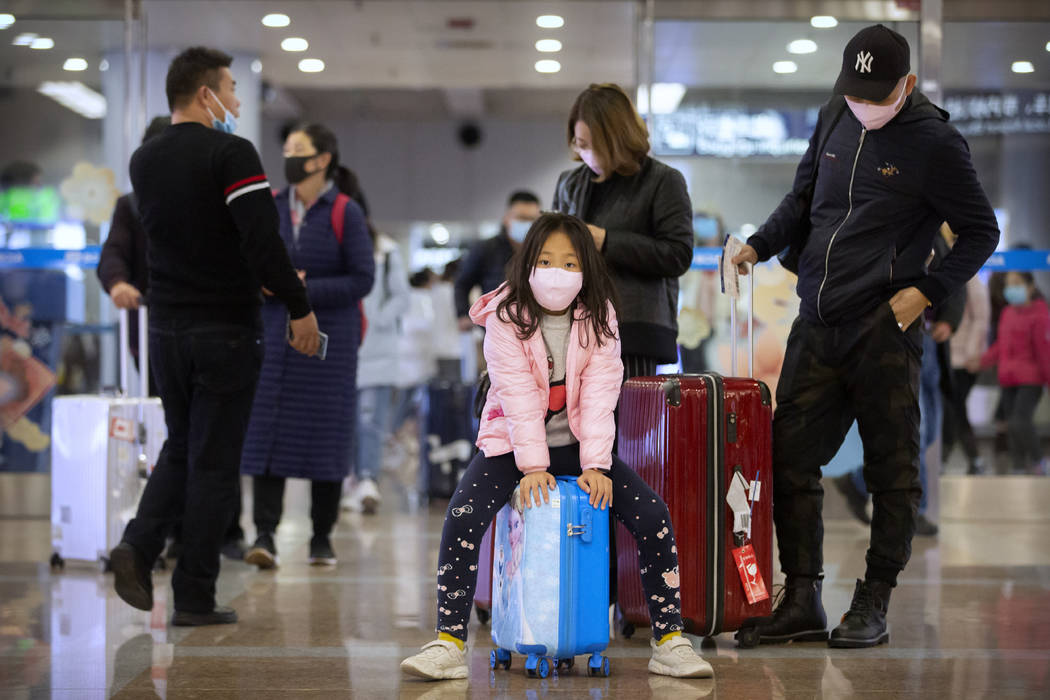 Travelers wear face masks as they stand in the arrivals area at Beijing Capital International A ...