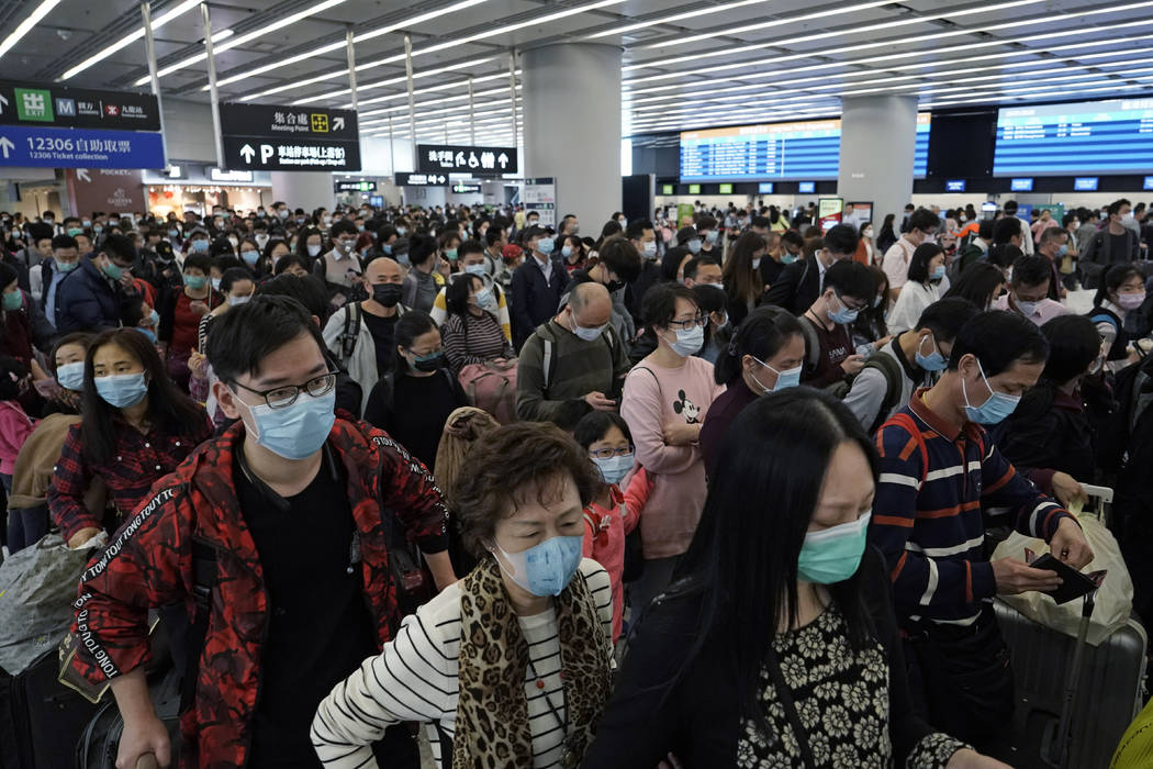 Passengers wear protective face masks at the departure hall of the high speed train station in ...