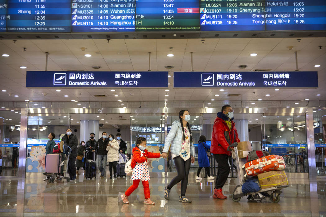 Travelers in face masks walk past a display board showing a canceled flight from Wuhan at Beiji ...