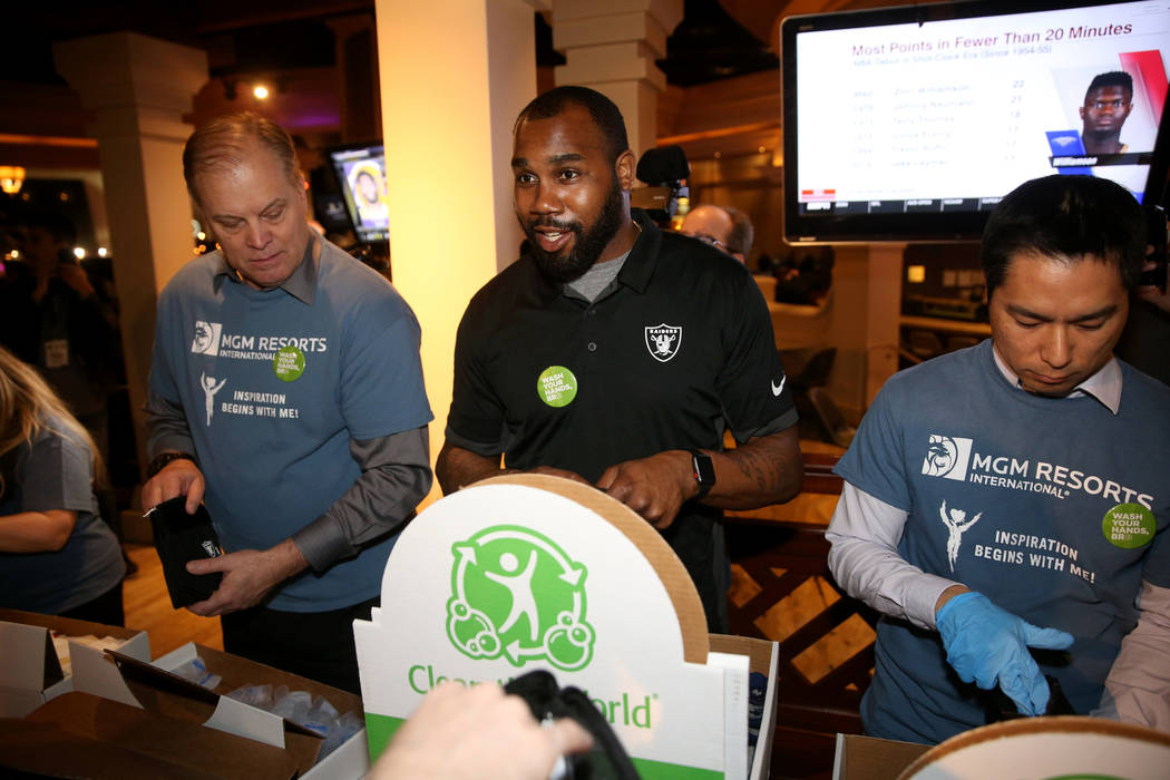 Raiders great Darren McFadden, center, makes hygiene kits with MGM employees Johnny Cox, left, ...