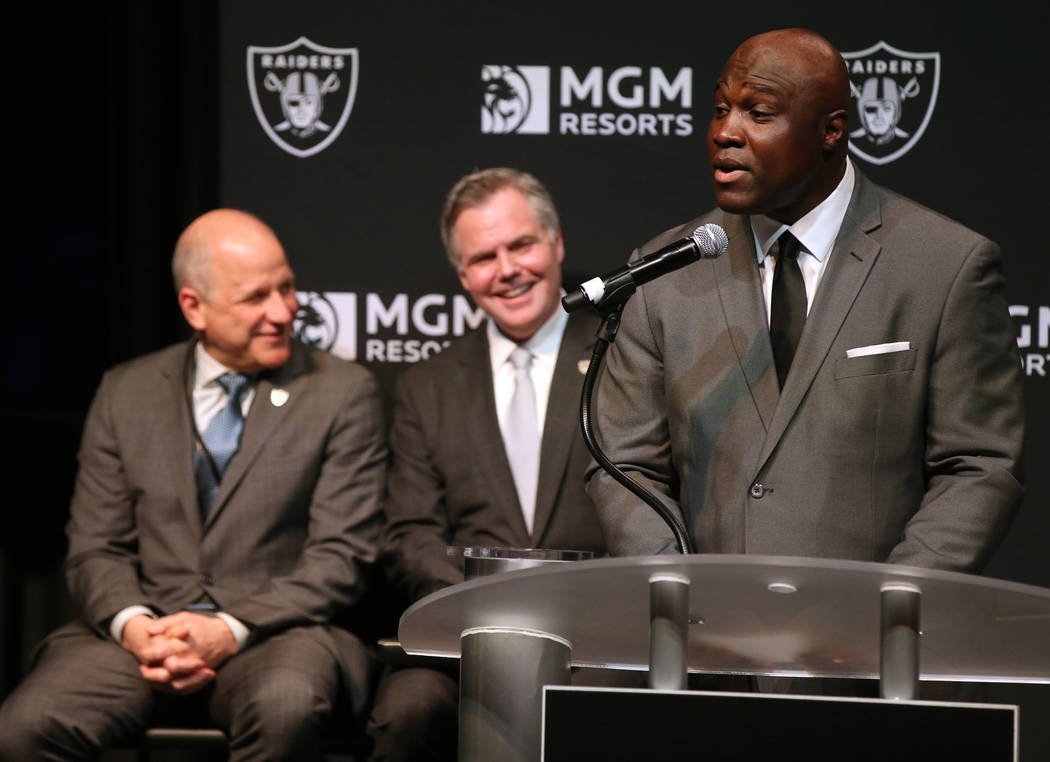 Raiders President Marc Badain, left, and Jim Murren, MGM Resorts CEO and chairman, look on as T ...