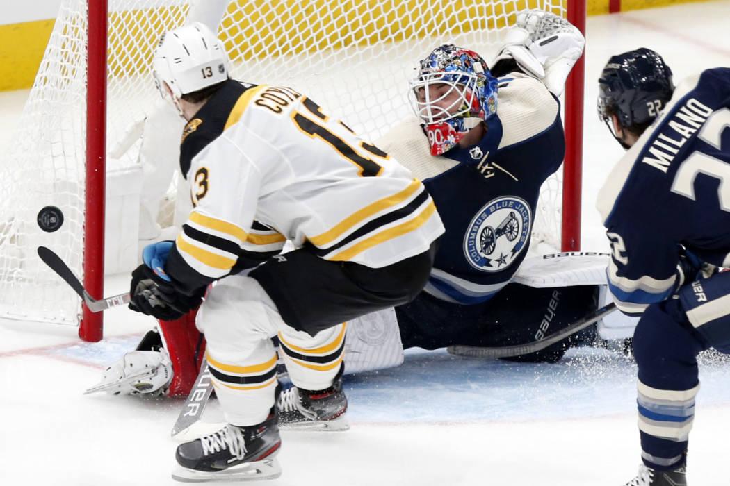 Columbus Blue Jackets goalie Elvis Merzlikins, center, of Latvia, stops a shot by Boston Bruins ...