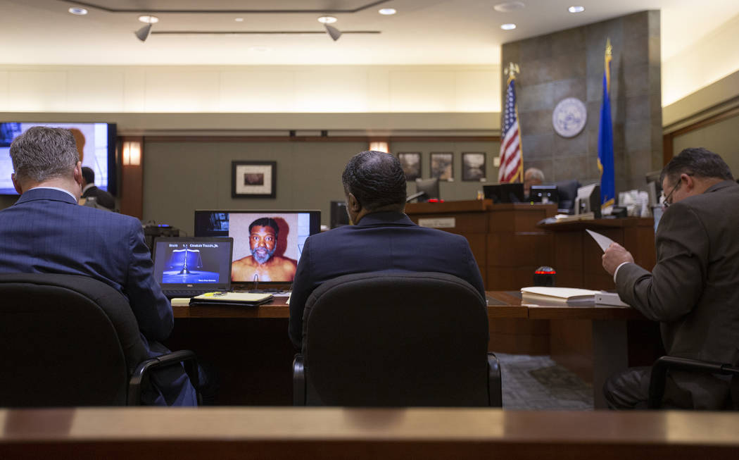Charles Talley Jr. is surrounded by his lawyers Michael Hyte, left, and Clark Patrick, right, d ...