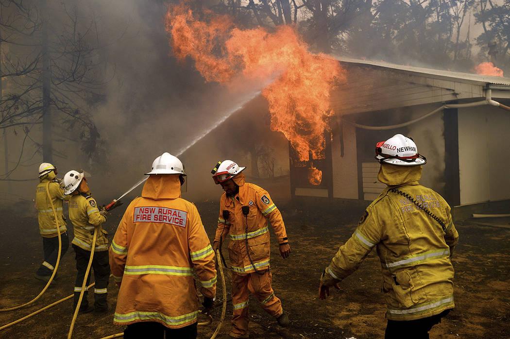 Firefighters battle the Morton Fire as it burns a home near Bundanoon, New South Wales, Austral ...