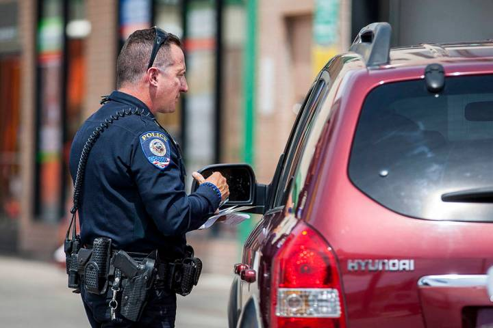 Officer Anthony Gaspardi of the Clark County School District Police gives a motorist a ticket o ...