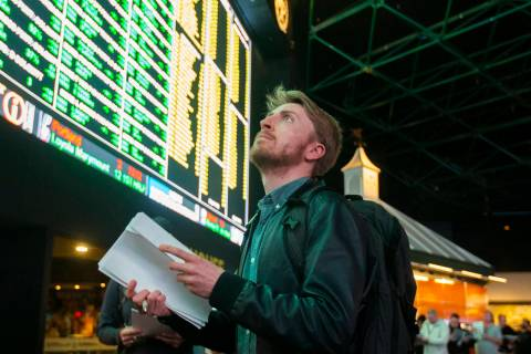 Rufus Peabody, middle, from Boston, waits in line at Westgate Sportsbook as Super Bowl prop bet ...