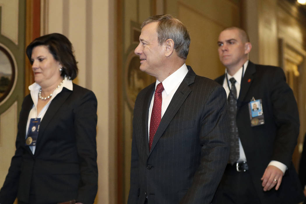 Supreme Court Chief Justice John Roberts, center, arrives at the Capitol in Washington for the ...