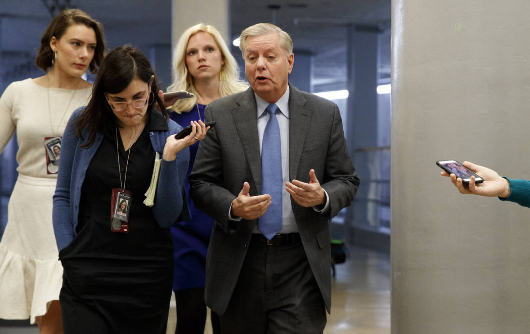 Sen. Lindsey Graham, R-S.C., right, answers reporters' questions, Friday, Jan. 24, 2020, on Cap ...