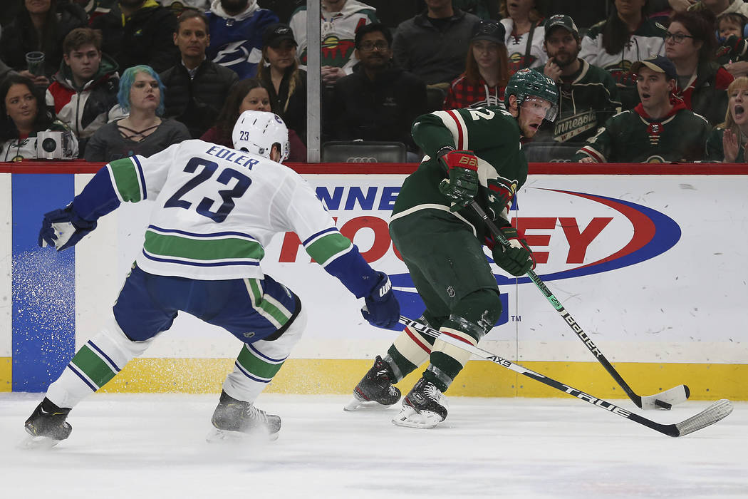 Minnesota Wild's Eric Staal, right, controls the puck against Vancouver Canucks' Alexander Edle ...