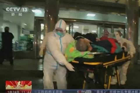 In this Thursday, Jan. 23, 2020, image from China's CCTV video, a patient is carried on a stret ...