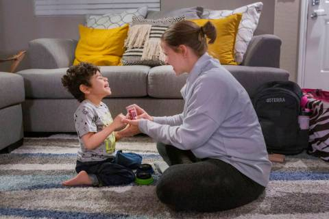 Rio Hansen, 3, works with Steffany Card, a speech-language pathologist, during a therapy sessio ...