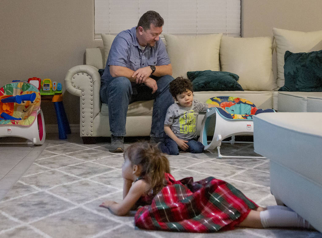 Mike Hansen sits with his children, Luna 2, as she watches a movie, and Rio, 3, plays, at their ...