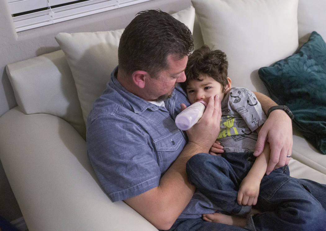 Mike Hansen gives his son, Rio, 3, PediaSure before Rio is put to sleep, in their home in Hende ...