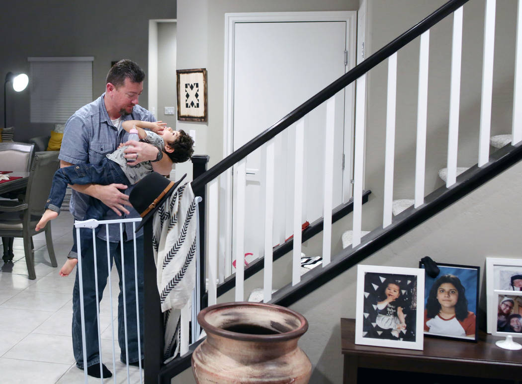 Mike Hansen brings his son Rio, 3, up to bed in their home in Henderson on Wednesday, Dec. 18, ...