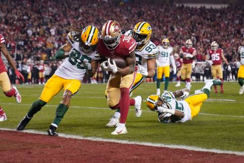 San Francisco 49ers running back Raheem Mostert, center, scores a touchdown next to Green Bay P ...