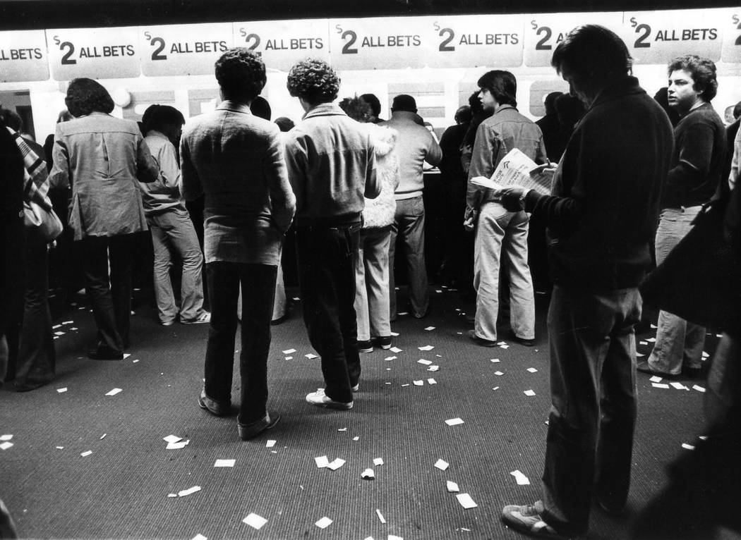 Bettors line up at windows at the Dunes race and sportsbook in a photograph from November 1981. ...