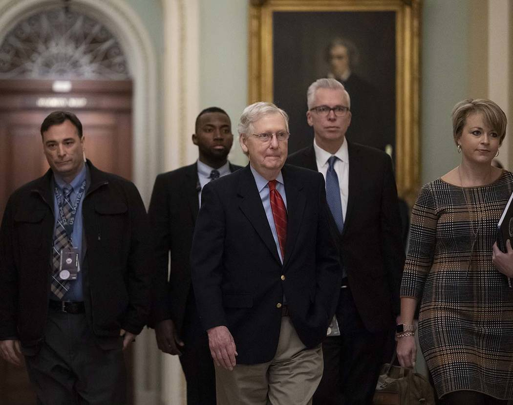 Senate Majority Leader Mitch McConnell, R-Ky., arrives at the chamber as work resumes in the im ...