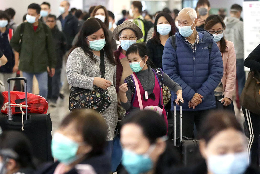 Passengers wearing protective face masks enter the departure hall of a high speed train station ...