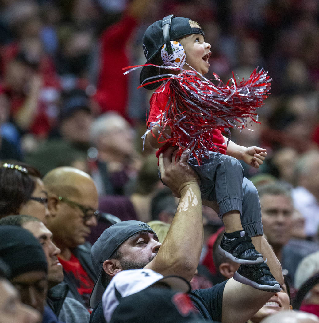 A young UNLV Rebels fan is hoisted up while cheering for the team versus the San Diego State Az ...