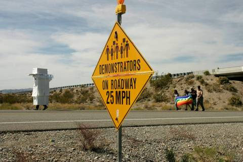 Anti-nuclear demonstrators, some in costume, pass by a sign that warns motorists of their prese ...