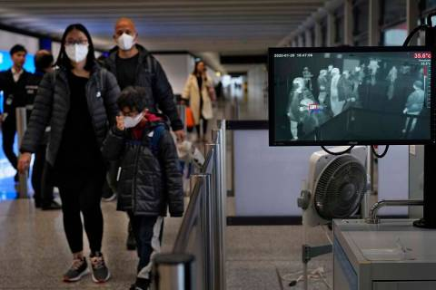Health surveillance officer use temperature scanner to monitor passengers arriving at Hong Kong ...